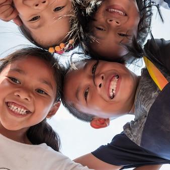 Lage hoek schot van opgewonden kinderen staan in cirkel knuffelen camera kijken naar samen spelen, team van lachende kinderen omhelzen samen in een cirkel. portret van jonge jongen en meisjes die camera bekijken