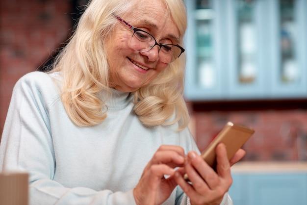 Lage hoek senior vrouw mobiel gebruiken