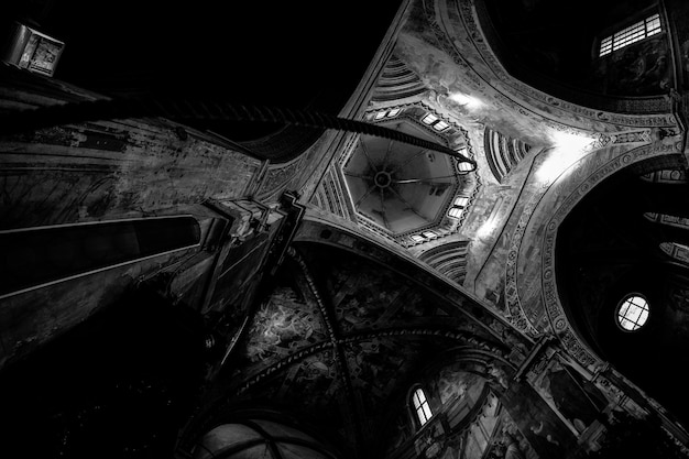 Lage hoek shot van een gebogen type plafond met een touw naar beneden in zwart-wit