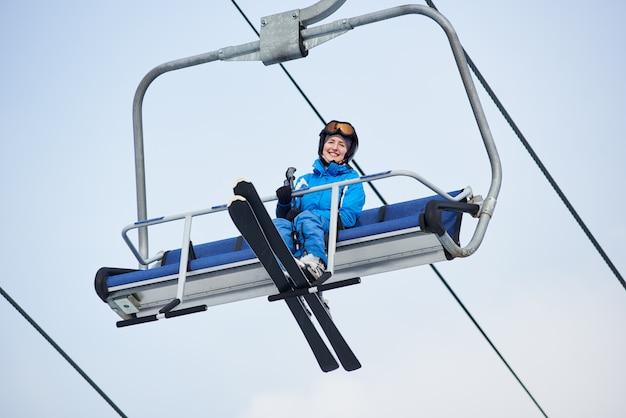 Lage hoek shot van een glimlachende vrouwelijke skiër in blauw skikostuum rijden tot aan de top van de berg op een kabel-skilift