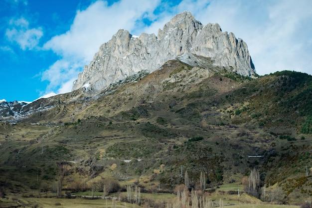 Lage hoek shot van een hoge rotsachtige klif op de top van een berg onder een bewolkte hemel