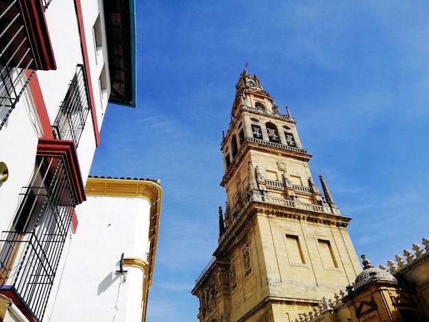 Lage hoek shot van een klokkentoren in de grote moskee-kathedraal van córdoba in spanje met een blauwe hemel