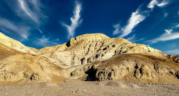 Lage hoek shot van een rotsformatie in death valley in californië, verenigde staten onder de bewolkte blauwe hemel