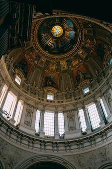 Lage hoek shot van het prachtige plafond en de ramen en schilderijen in een oud gebouw