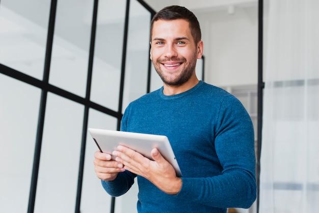 Lage hoek smilet man met tablet