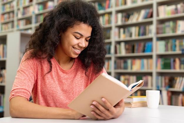Lage hoek smiley tienermeisje lezen