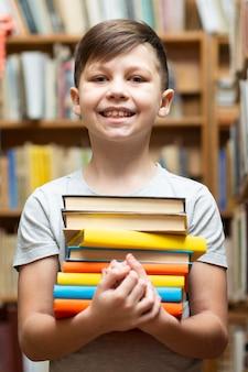 Lage hoek smileyjongen met stapel boeken