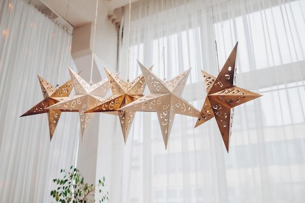 Lage hoek stock foto van vijf papier of metalen decoratieve sterren opknoping tegen wit gordijn op het raam bij daglicht.