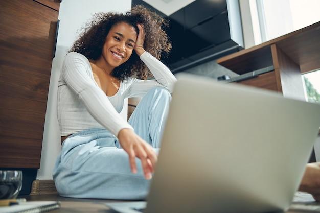 Lage hoek van een gelukkige vrouwelijke freelancer met haar hoofd gestut op haar hand zittend op de vloer