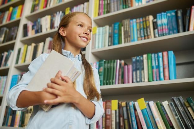 Lage hoek van een glimlachend mooi schoolkind met een stapel boeken die in de verte kijken