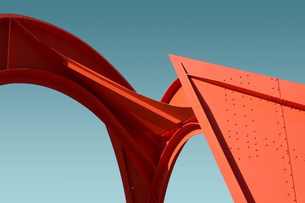Lage hoek van een metalen rode structuur onder de heldere blauwe hemel