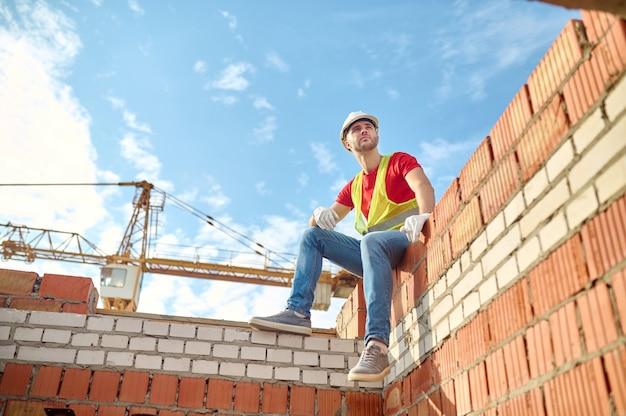 Lage hoek van een serene metselaar in een veiligheidsvest en een veiligheidshelm zittend op de muur van een half afgebouwd huis