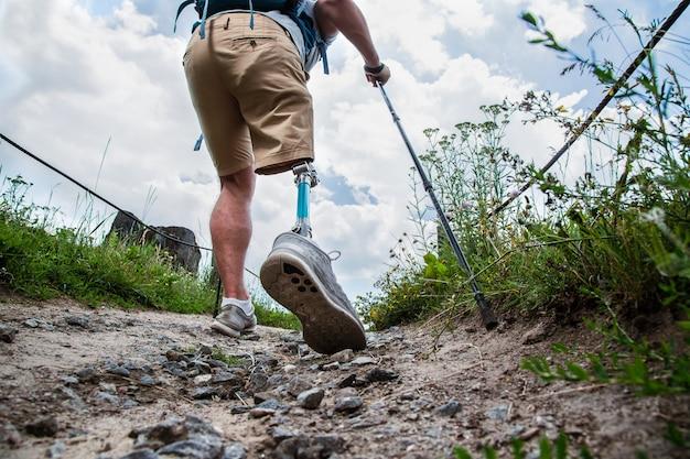 Lage hoek van een sportieve gehandicapte man met prothese die langs het pad loopt terwijl hij een gezonde manier van leven leidt