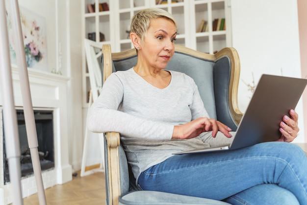 Lage hoek van een verraste kortharige oude dame die aan een computer in een fauteuil werkt