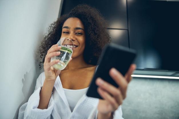 Lage hoek van een vrolijke vrouw met een gezond drankje die naar haar smartphone kijkt