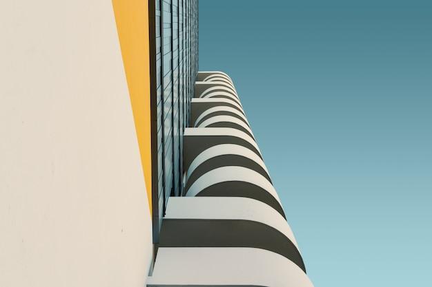 Lage hoek van een wit betonnen gebouw onder de heldere blauwe hemel