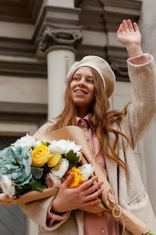 Lage hoek van elegante vrouw buitenshuis boeket bloemen te houden in de lente
