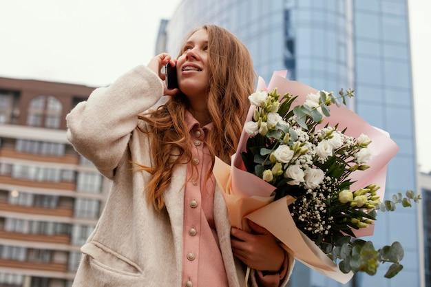 Lage hoek van elegante vrouw buitenshuis praten aan de telefoon en met een boeket bloemen