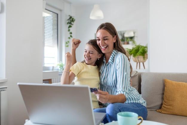 Lage hoek van gelukkige kleine dochter met opgeheven armen vreugde terwijl glimlachende moeder in casual kleding gericht op het scherm en het gebruik van laptop voor online winkelen in licht modern appartement