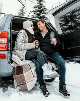 Lage hoek van het gelukkige paar met een warm drankje in de kofferbak van de auto tijdens een roadtrip