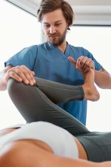 Lage hoek van osteopathisch therapeut die de beenbeweging van de vrouwelijke patiënt controleert