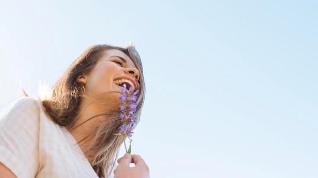 Lage hoek van smiley vrouw met bloem en kopie ruimte