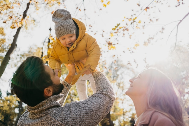 Lage hoek van vader en moeder met baby buitenshuis