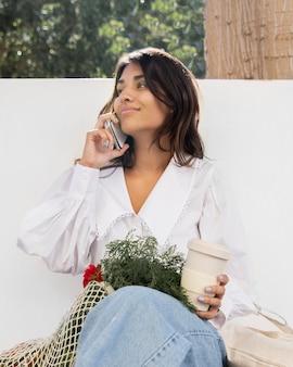 Lage hoek van vrouw praten aan de telefoon buitenshuis tijdens het drinken van koffie