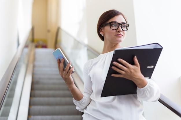 Lage hoek van zakenvrouw met bindmiddel en smartphone op roltrap