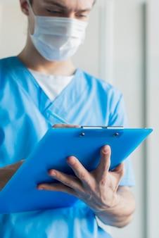 Lage hoek verpleegkundige man met klembord