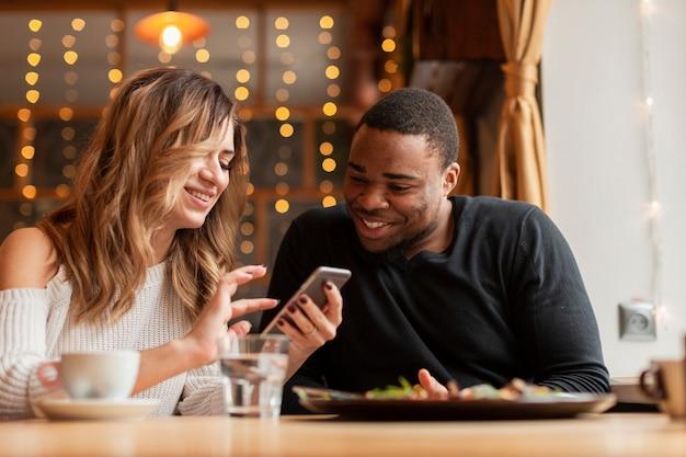 Lage hoek vrienden kijken op mobiel