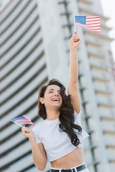 Lage hoek vrouw met twee usa vlaggen en glimlachen