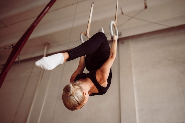 Lage hoek vrouw training op gymnastiek ringen