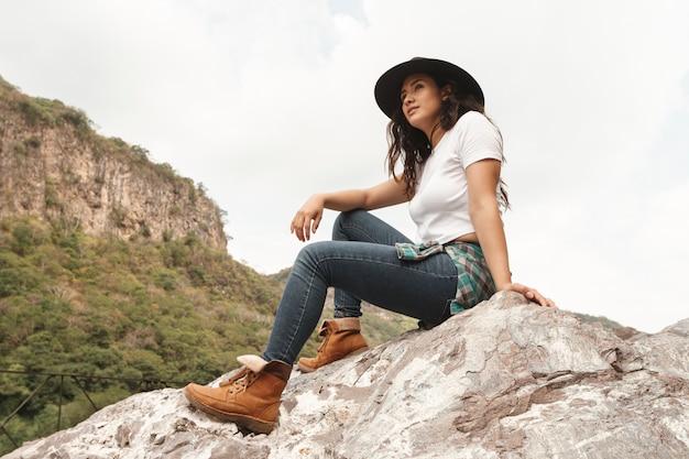 Lage hoek vrouwelijke ontdekkingsreiziger op rotsen