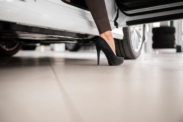 Lage hoek vrouwelijke verkopende auto's