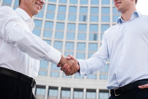 Lage hoek zakenlieden handen schudden