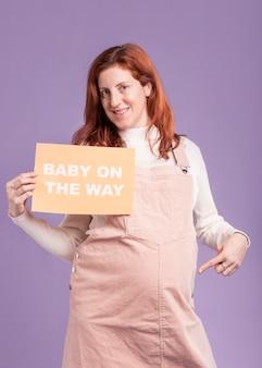 Lage hoek zwangere vrouw wijzend op papier met baby onderweg bericht