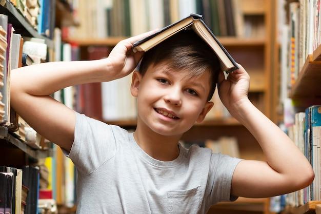 Lage hoekjongen met boek op hoofd