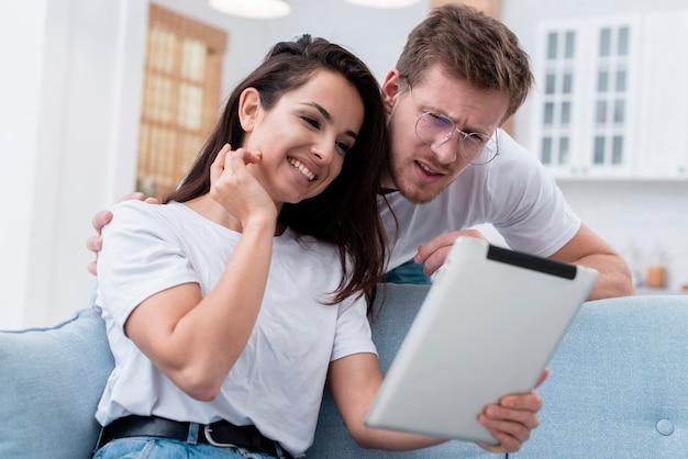 Lage hoekman en vrouw die op tablet kijken