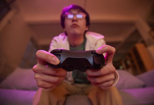 Lage hoekmening bij aziatische jongeman die gamepad vasthoudt en thuis videogames speelt, verlicht door paars licht, kopieer ruimte