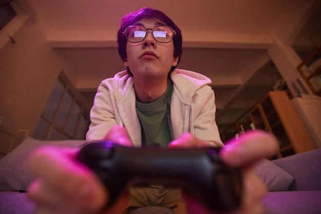 Lage hoekmening bij jonge aziatische man die gamepad vasthoudt terwijl hij thuis videogames speelt, verlicht door paars licht