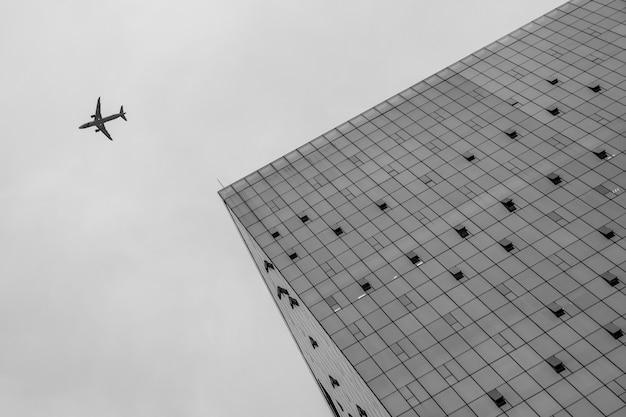 Lage hoekmening naar een gebouw en een vliegtuig dat er dichtbij in de lucht vliegt
