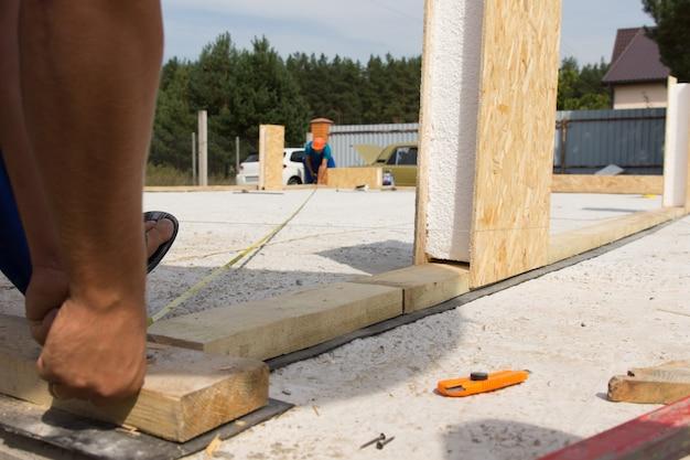 Lage hoekmening op vloerniveau van achteren van twee werklieden die metingen doen op een bouwplaats over de fundering en vloer van een nieuwbouwhuis