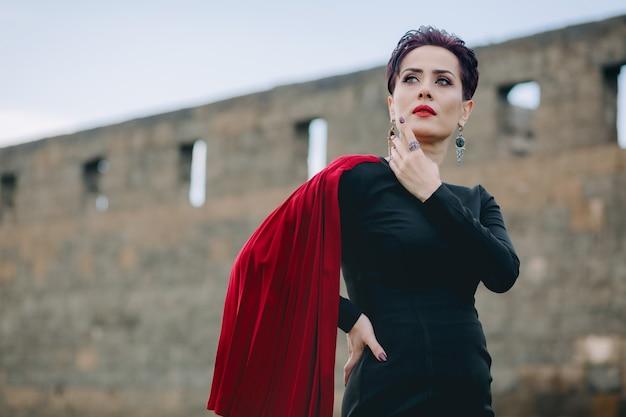 Lage hoekmening van aantrekkelijke en prachtige vrouw met rode mantel en zwarte jurk poseren voor het oude kasteel met donkere wolken