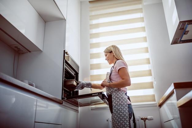 Lage hoekmening van aantrekkelijke kaukasische blonde huisvrouw in schort die gebakken diner uit oven nemen.