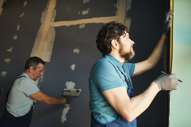 Lage hoekmening van bouwploeg die in de kamer werkt tijdens het bouwen of renoveren van huis, kopie ruimte
