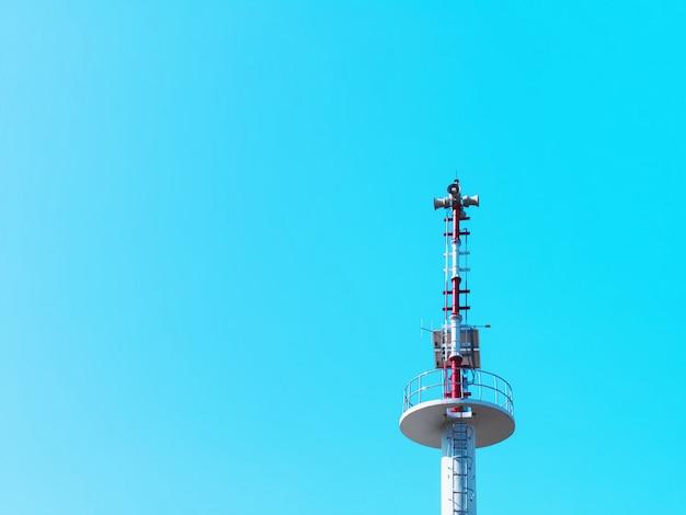 Lage hoekmening van communicatie toren tegen blauwe hemel