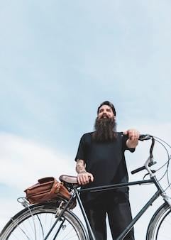 Lage hoekmening van een gebaarde mens die zich met zijn fiets tegen blauwe hemel bevindt