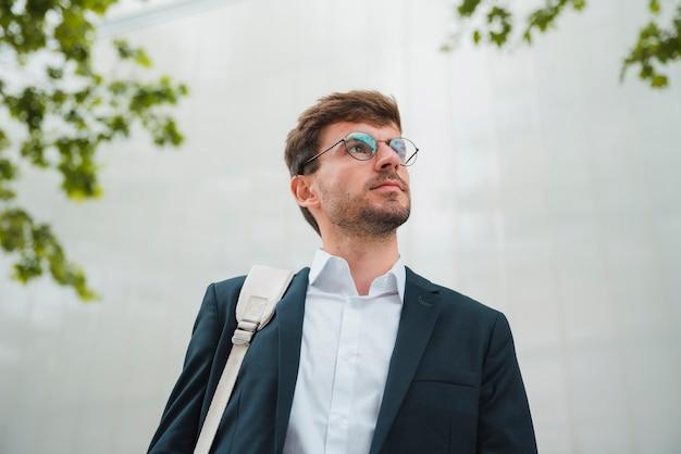 Lage hoekmening van een jonge zakenman die zich tegen muur bevindt die weg eruit ziet