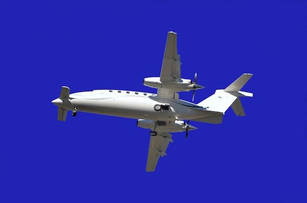 Lage hoekmening van een vliegtuig dat onder het zonlicht en een blauwe hemel overdag vliegt